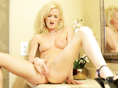 Sweet young blonde babe is passionately masturbating her pussy on windowsill